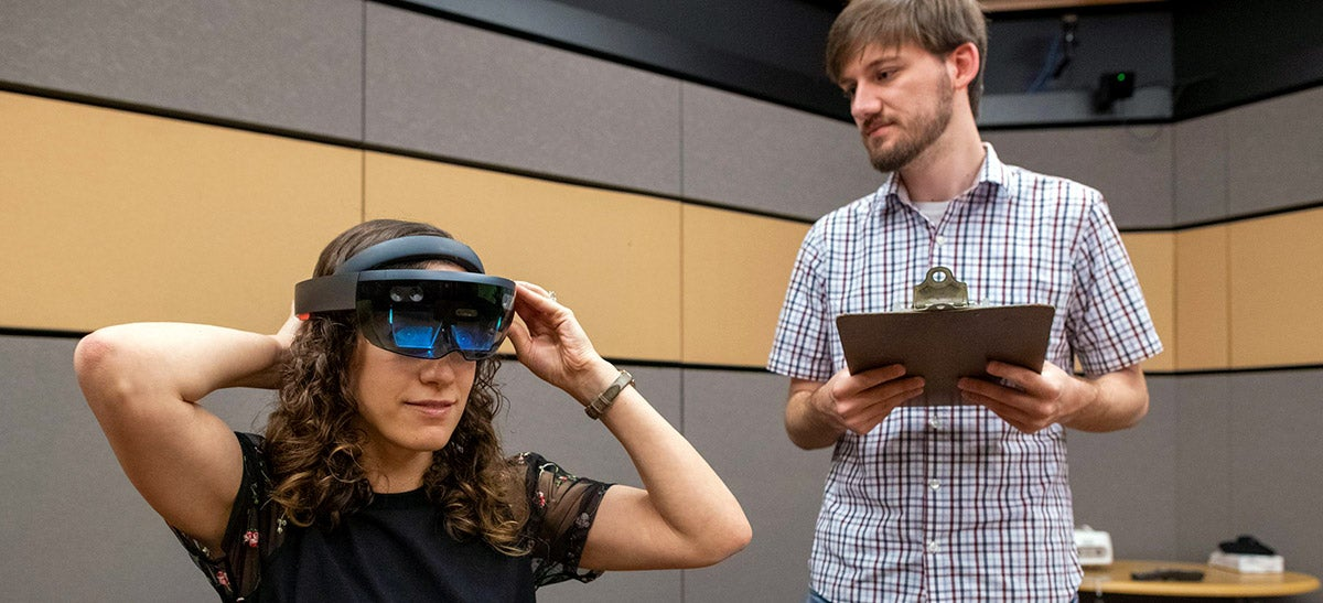 A graduate student works with lab manager through the augmented reality experiment during a testing phase.